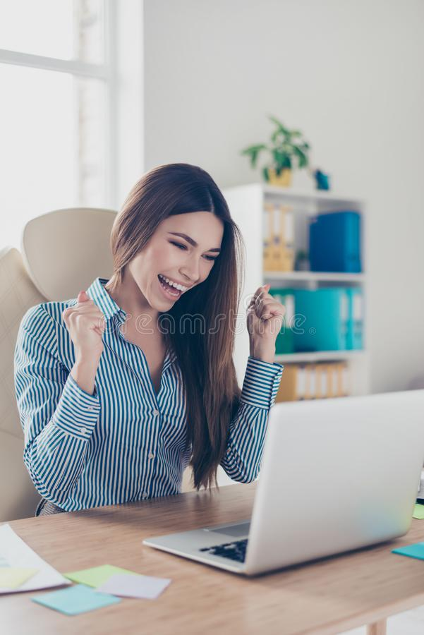 Cheerful attractive business lady economist is celebrating the b. Reakthrough of her company`s strategy. She is in a smart striped shirt, sitting at her work royalty free stock photo
