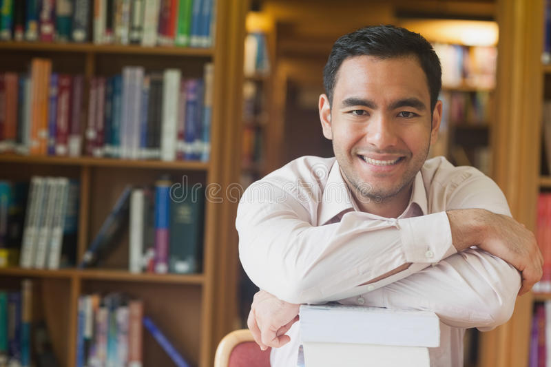 Cheerful attractive man posing leaning on a stack of books in library