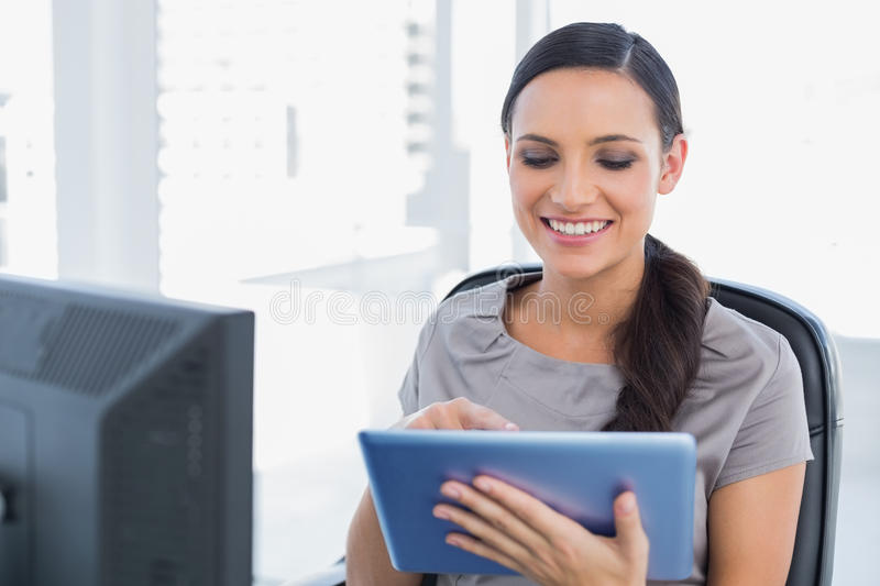 Cheerful attractive secretary scrolling on tablet pc