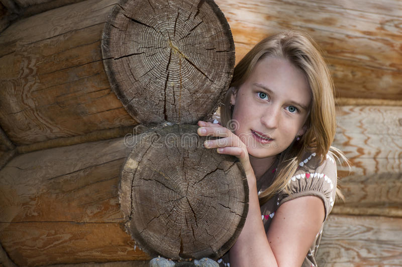 Cheerful attractive teen girl near the wooden house