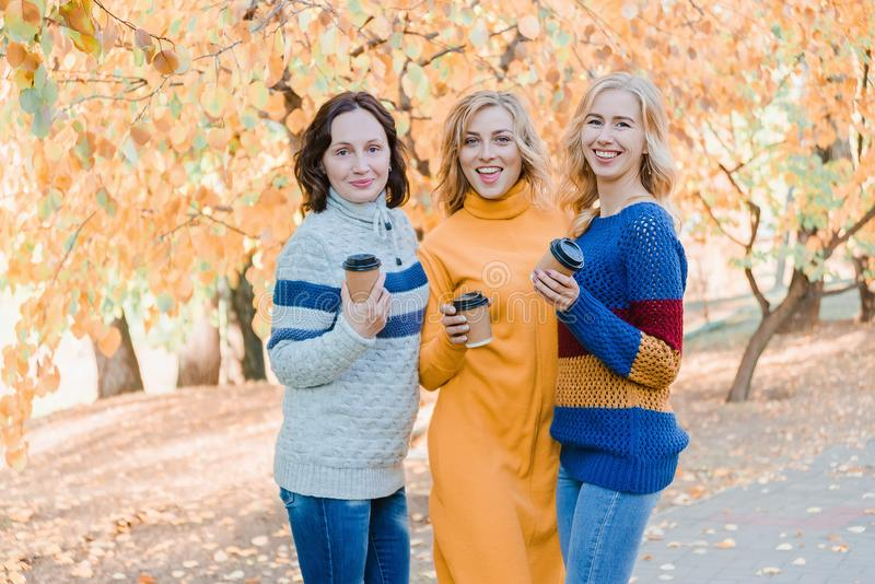 Cheerful attractive three young women best friends having fun together outside. stock photo