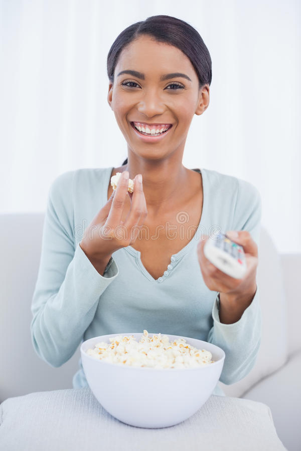 Download Cheerful Attractive Woman Eating Popcorn While Watching Tv Stock Photo - Image: 32970114