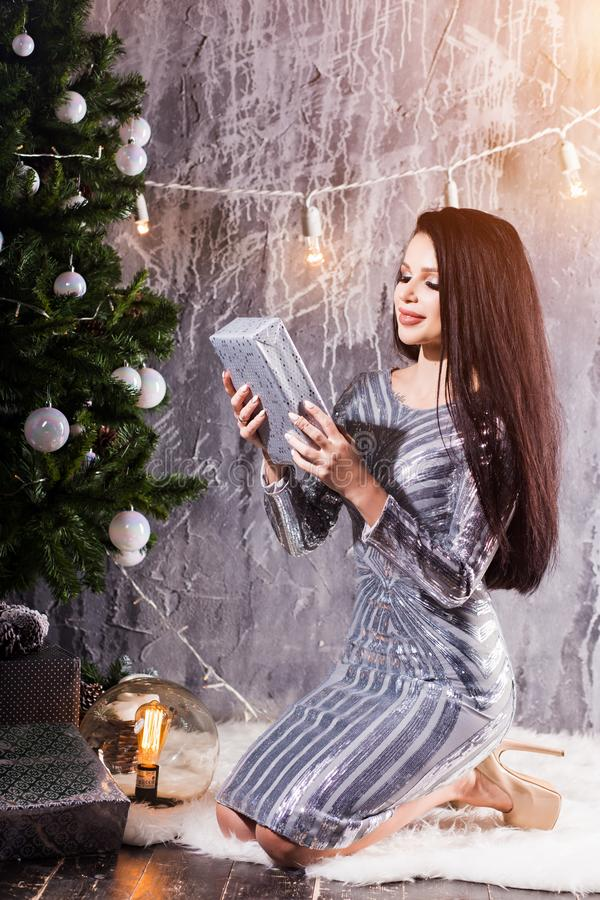 Cheerful attractive woman in silver dress having fun while sitting near a Christmas tree looking for gifts. New Year, holiday, celebration, winter concepts stock images