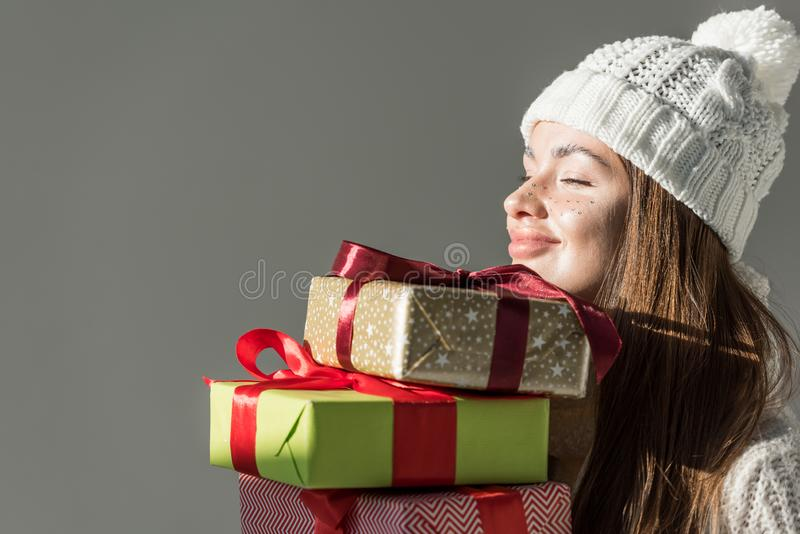 cheerful attractive woman in stylish winter sweater and scarf holding gift boxes isolated stock photos
