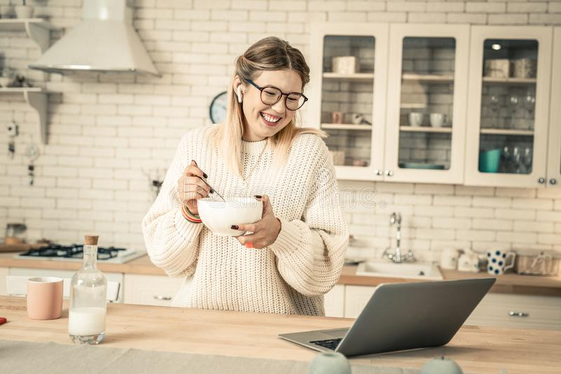 Cheerful attractive woman with wide smile carrying bowl with breakfast stock photo