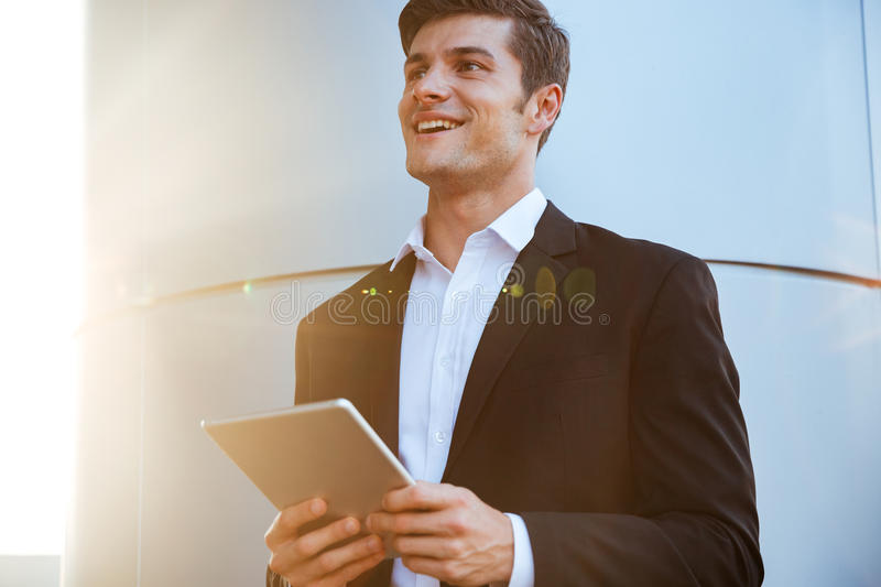 Cheerful attractive young businessman standing outdoors and using tablet stock images