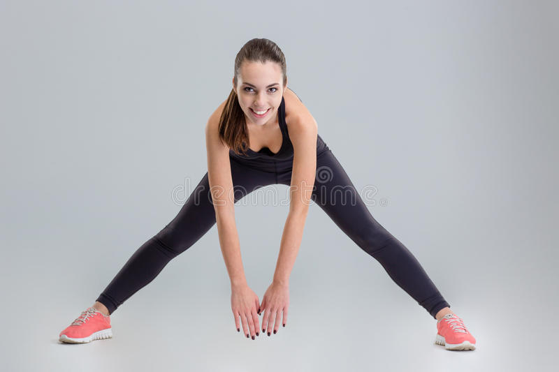 Cheerful attractive young fitness woman doing exercises and looking camera stock photos