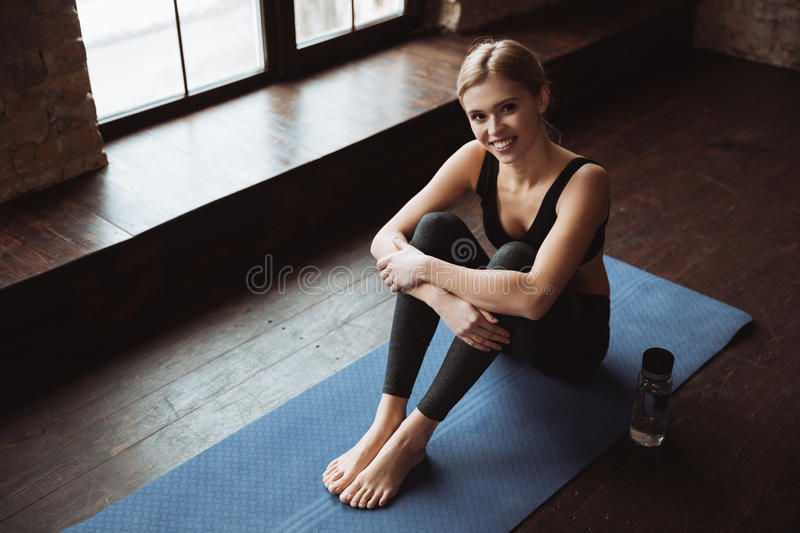 Cheerful attractive young fitness woman sitting on yoga mat royalty free stock image