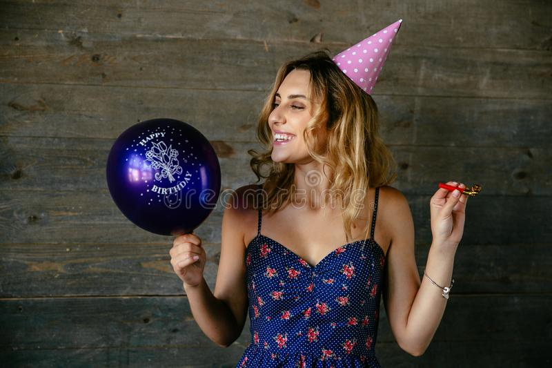 Beautiful woman celebrating birthday party. Cheerful attractive young woman celebrating birthday, holding balloons, pipe whistle, wearing festive hat. Holiday royalty free stock image