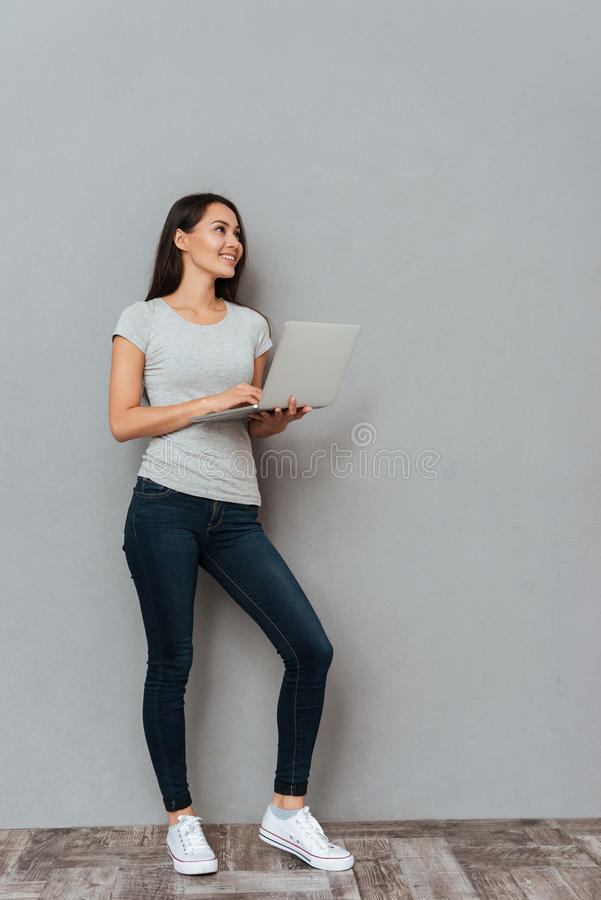 Cheerful attractive young woman holding laptop and looking away. Over grey background royalty free stock photo