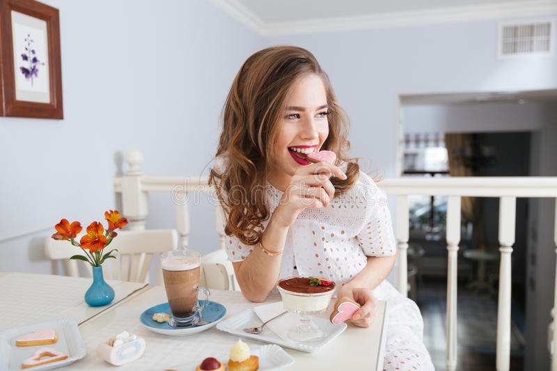 Cheerful attractive young woman sitting and eating heart shaped cookies stock images