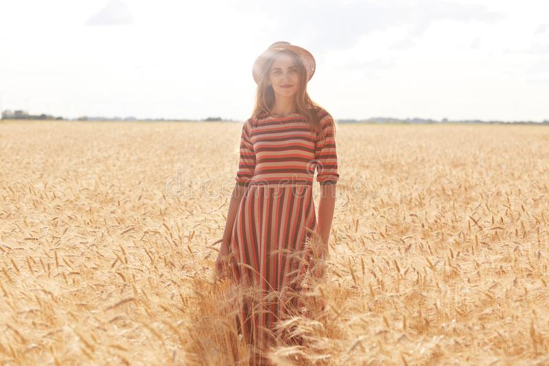 Cheerful attractive young woman standing straight in filed at rural area, feeling nature, being inspired with landscape, having stock image