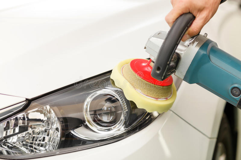 Cheerful auto service worker is burnishing the. Close up of hand of man polishing a car with the equipment royalty free stock image