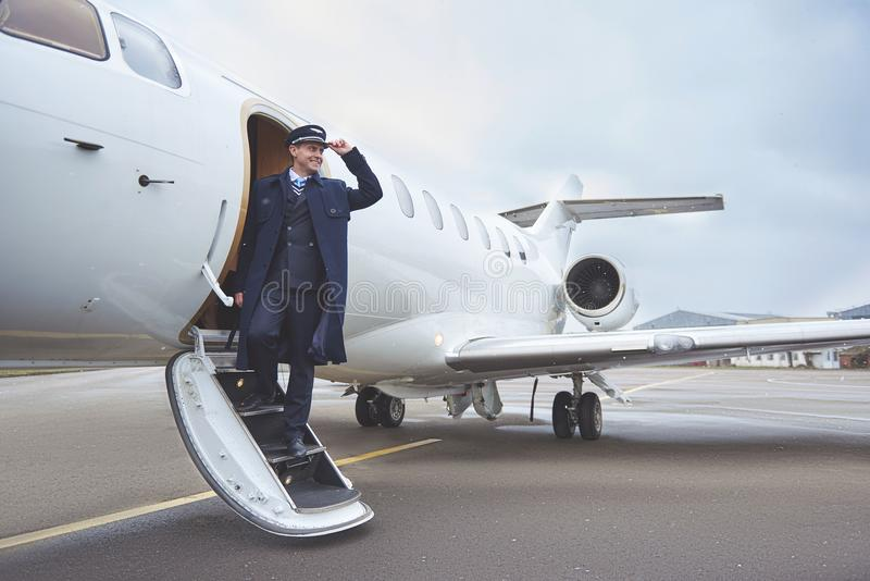 Cheerful aviator situating near plane stock photos