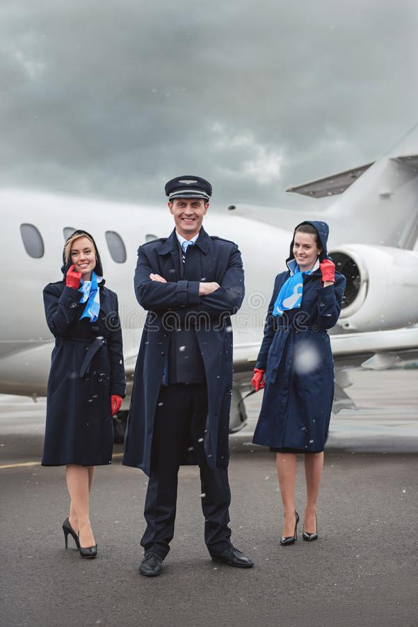Cheerful aviator and stewardesses looking at camera stock images
