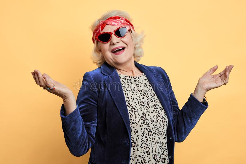 Cheerful awesome cool granny with raised hands royalty free stock photography