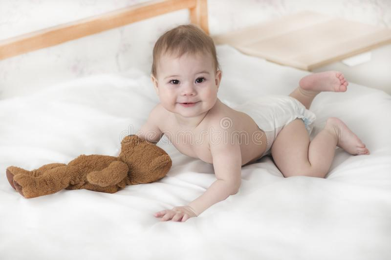 Cheerful baby boy girl in a diaper lying with a teddy bear. Cute baby in a diaper crawling on the bed, look into the camera stock photography
