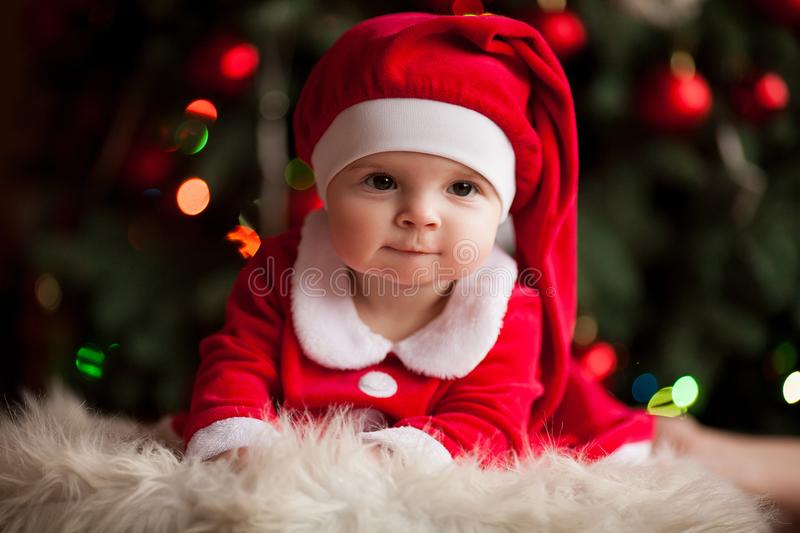 Cheerful baby girl in Santa Claus costume lies on fur rug against background of Christmas decorations. stock images