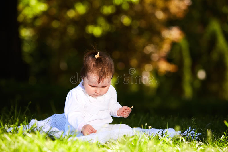 Cheerful baby girl sitting on the green grass in the city park at summer day. stock photo