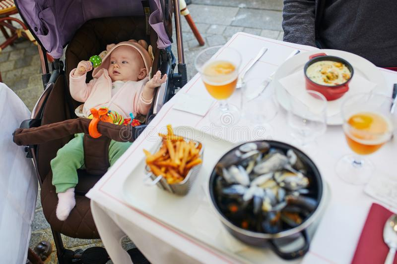 Cheerful baby girl in stroller in restaurant royalty free stock photography