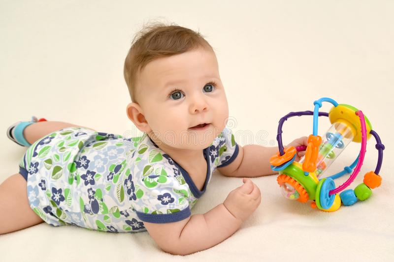The cheerful baby holds a toy lying on a stomach royalty free stock photos
