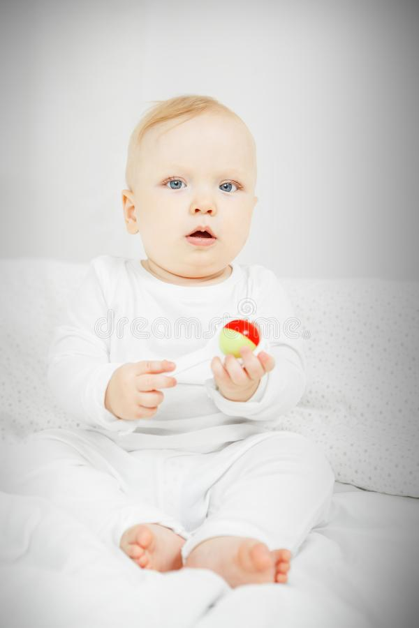 Cheerful baby sits on bed and holds rattle. Cute cheerful baby with big light eyes and blond hair sits in playful mood and holds rattle in form of flower stock image