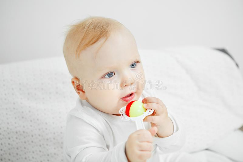 Cheerful baby sits on bed and holds rattle. Cute cheerful baby with big light eyes and blond hair sits in playful mood and holds rattle in form of flower stock photos