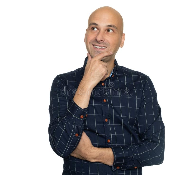 Cheerful bald man looking up and thinking. Isolated stock photography