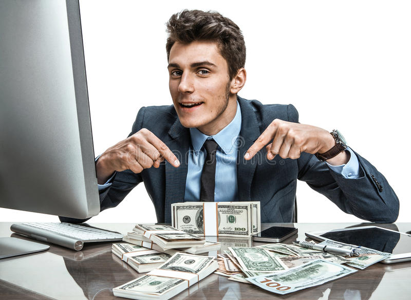 Cheerful banker showing his dividend earnings, profit, income, gain, benefit, margin. Modern businessman at his desk with computer and a lot of money royalty free stock images