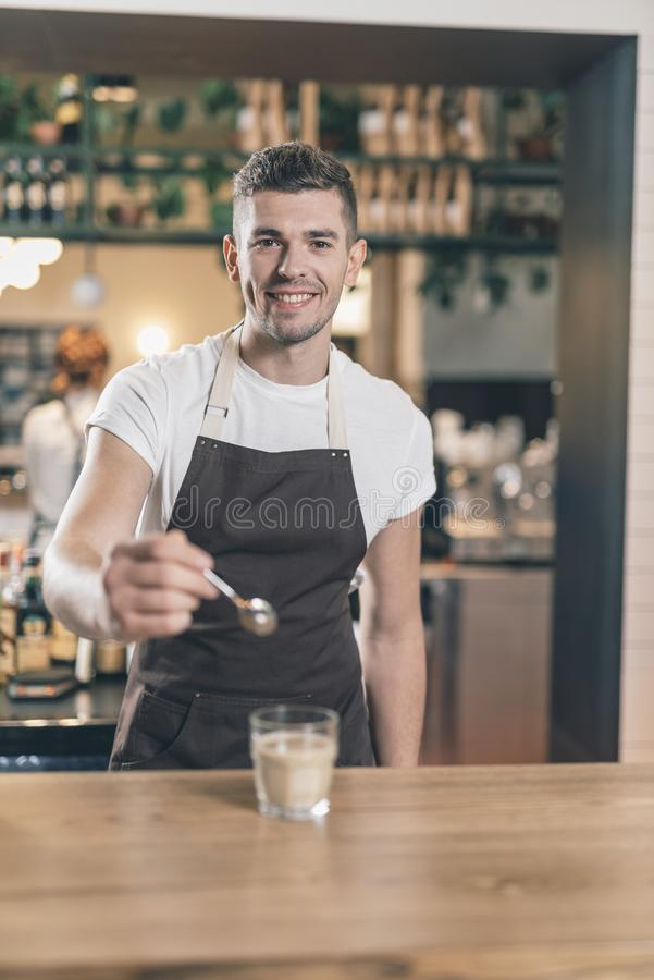 Cheerful barista at the bar counter holding teaspoon near the glass royalty free stock images