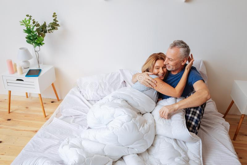 Cheerful beaming wife hugging her strong supportive man stock image