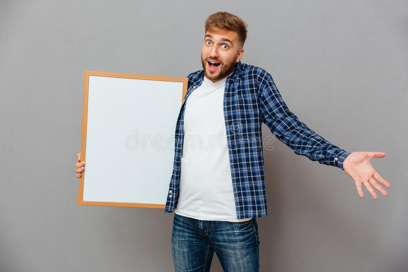 Cheerful bearded man holding blank board and shrugging shoulders. Isolated on a gray background stock photo