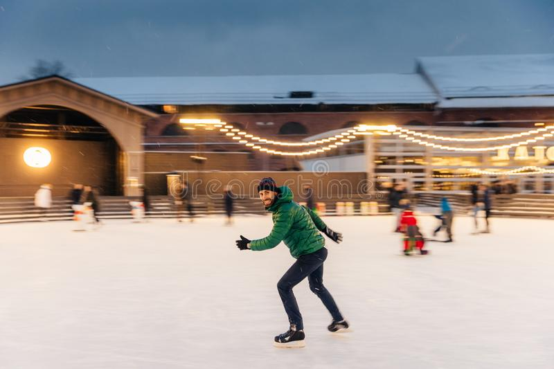 Cheerful bearded man spends Christmas time on majestic ice rink decorated with lights, skates on ice, has fun, enjoys his hobby an stock image