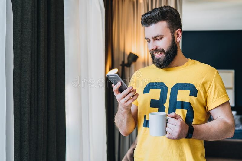 Cheerful bearded man stands in room and using smartphone. Guy laughs looking at screen of phone while drinking coffee. stock images