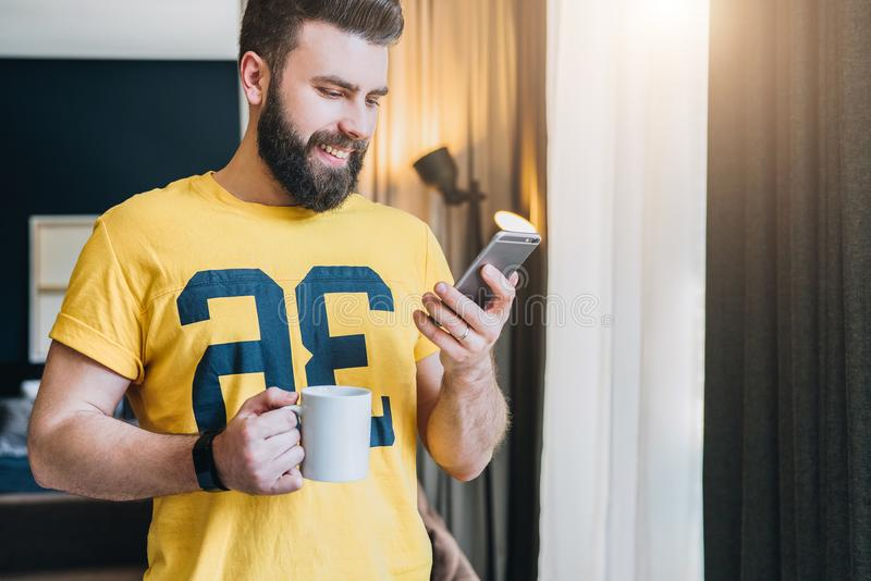 Cheerful bearded man stands in room and using smartphone. Guy laughs looking at screen of phone while drinking coffee. stock photo