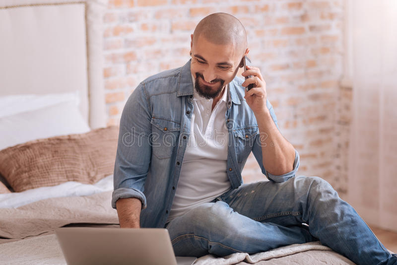Cheerful bearded man talking over the phone stock images