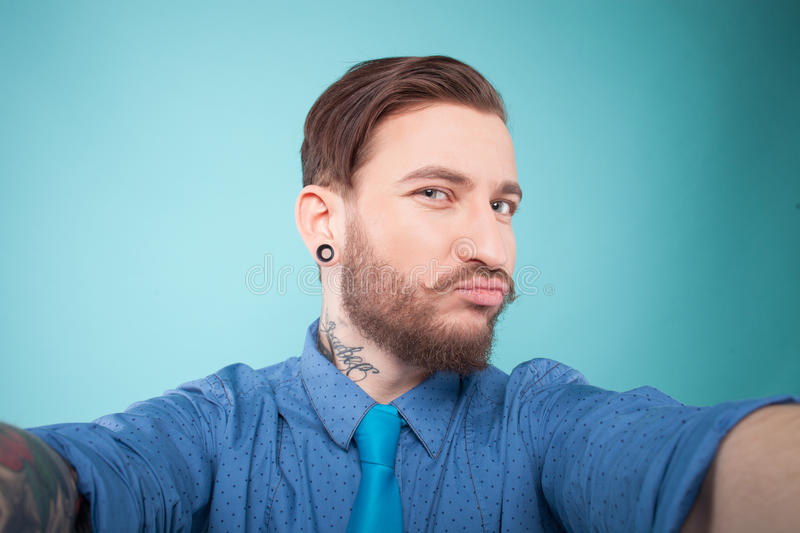 Cheerful bearded young guy is photographing. Cool hipster is making selfie with joy. He is stretching hands forward and drawing faces. The man is looking at stock photos