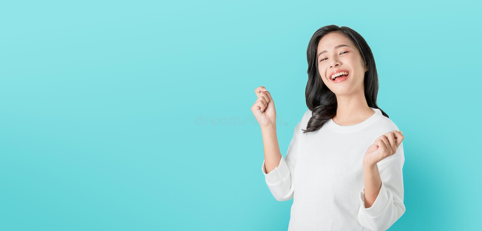 Cheerful beautiful Asian woman in casual white t-shirt and happy face smile on blue background. royalty free stock image