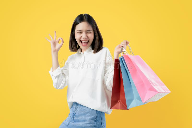 Cheerful beautiful Asian woman holding multi coloured shopping bags and shows ok sign on light yellow background. stock photography