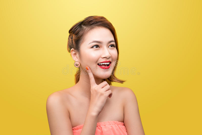 Cheerful beautiful asian young woman with charming smile over ye. Llow background. Beauty, fashion. Cosmetics royalty free stock photo