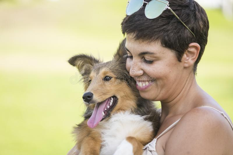 Cheerful beautiful caucasian woman carying a nice pet shetland dog with love and friendship. best friends forever concept with stock images