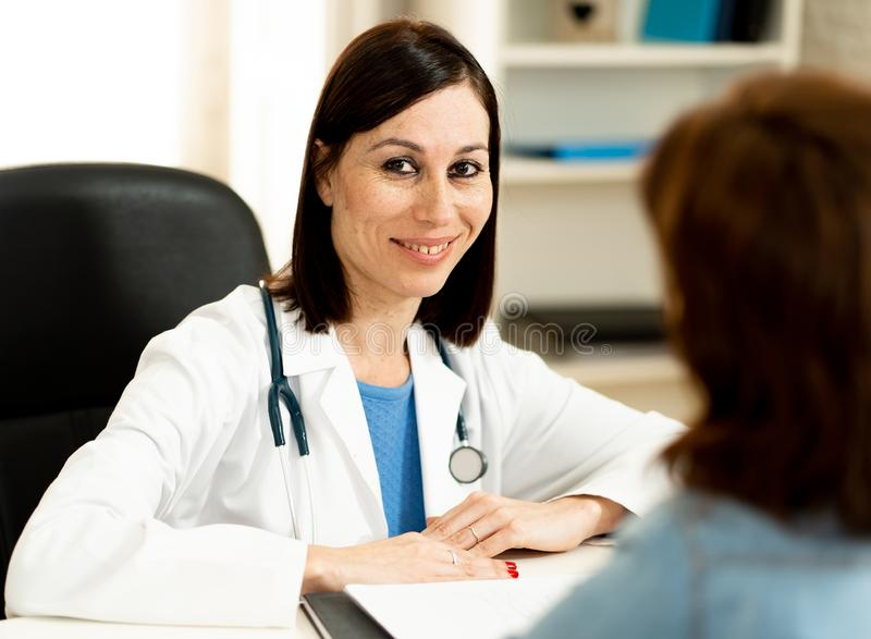 Cheerful beautiful doctor specialist at her hospital office with out of focus patient woman stock image