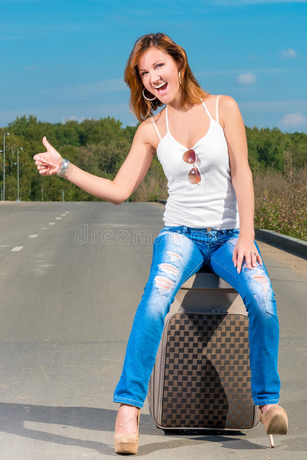 Cheerful beautiful girl catches passing car. Cheerful beautiful girl catches a passing car royalty free stock photo