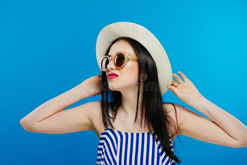 Cheerful beautiful girl in hat and sun glasses. Smiling widely, looking and pointing aside. Summer outfit. Waist up stock photos