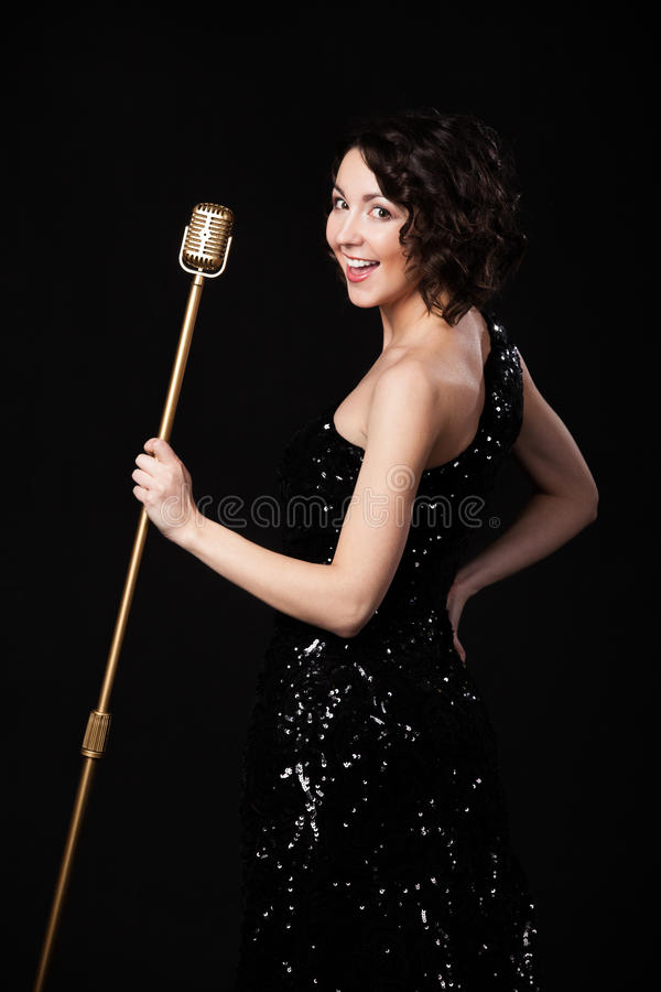 Cheerful beautiful girl singer holding golden vintage microphone royalty free stock photo