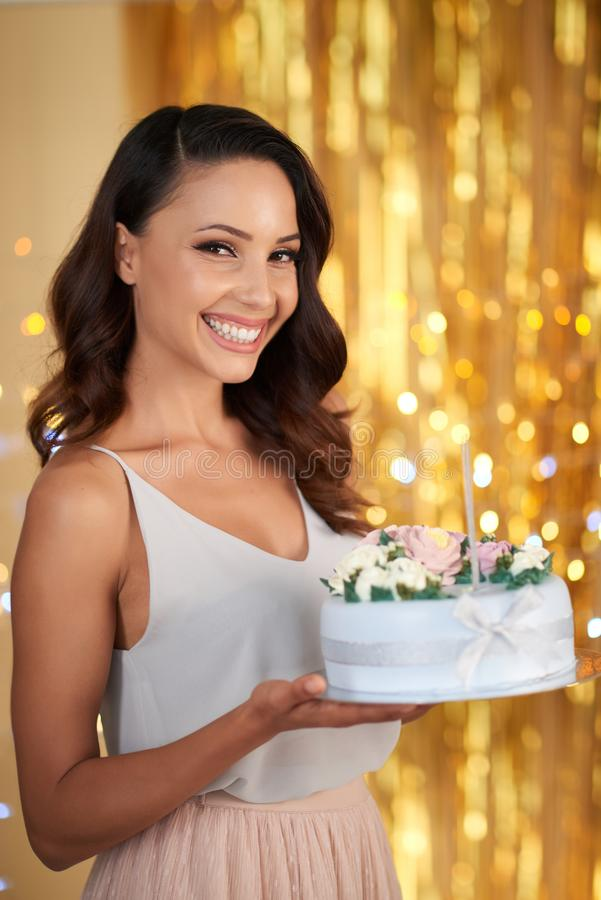 Cheerful beautiful party guest with cake royalty free stock image