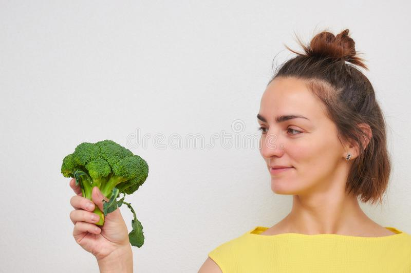 Cheerful, beautiful, slim, girl holding broccoli inflorescences in her hands isolated on a light background. woman of European stock photo