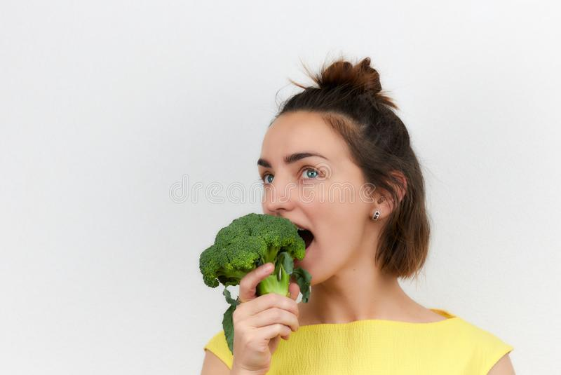 Cheerful, beautiful, slim, girl holding broccoli inflorescences in her hands isolated on a light background. woman of European royalty free stock photos