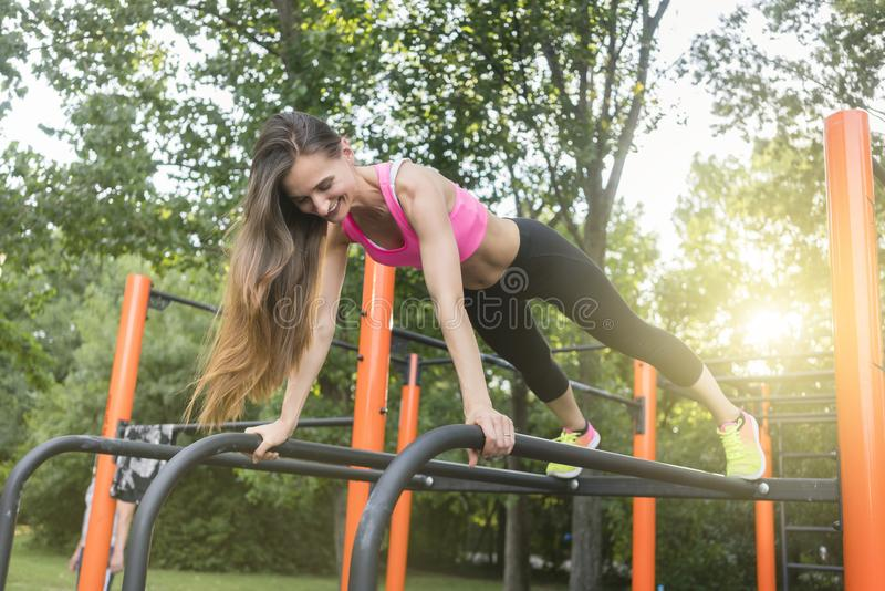 Cheerful beautiful woman exercising basic plank position outdoors. Low-angle view of a cheerful beautiful woman passionate about calisthenics training exercising royalty free stock photo