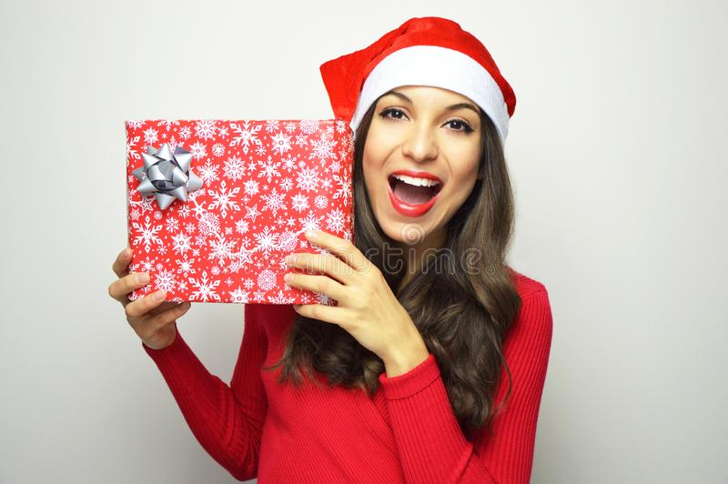 Cheerful beautiful woman with Santa Claus hat holding her christmas present on gray background stock photos